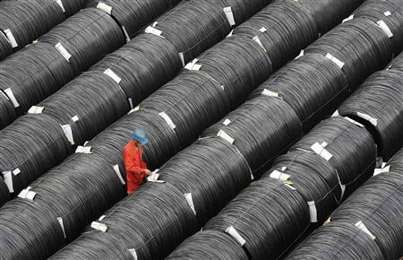 A worker checks on coils of steel at a factory in Dalian